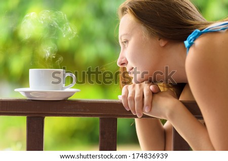 Young woman drinking cofee in a garden. Outdoors portrait. - stock photo