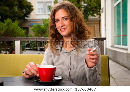 Young woman drinking coffee and smoking cigarette outdoors - stock photo