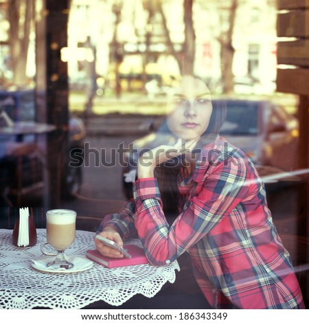 Young woman drinking coffee and use her smartphone sitting indoor in urban cafe. Cafe city lifestyle. Casual portrait of beautiful girl. Toned. - stock photo