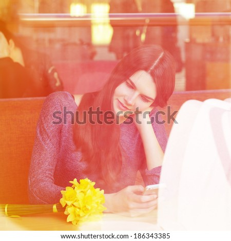 Young woman drinking coffee and use her smartphone sitting indoor in urban cafe. Cafe city lifestyle. Casual portrait of beautiful girl with spring flowers. Image toned. - stock photo