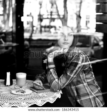 Young woman drinking coffee and use her smartphone sitting indoor in urban cafe. Cafe city lifestyle. Casual portrait of beautiful girl. Black and white - stock photo