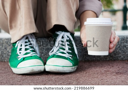 Young woman drinking coffee from disposable cup - stock photo