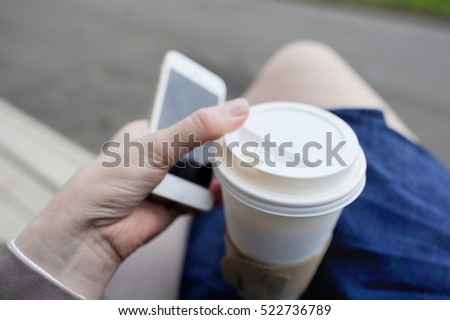 Young woman drinking coffee from disposable cup and using her smartphone