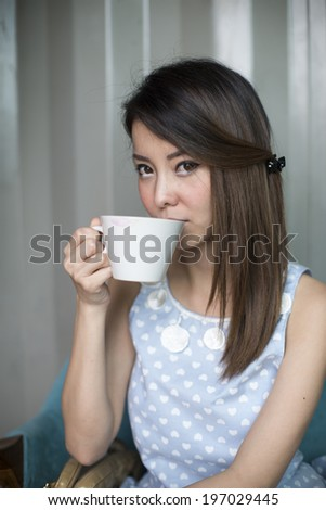 Young woman drinking coffee in a cafe - stock photo
