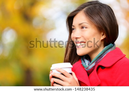 Young woman drinking coffee in Autumn. Fall woman outdoors in autumn forest foliage enjoying hot coffee or tea from disposable mug. Beautiful young female model, mixed race Asian Chinese / Caucasian. - stock photo