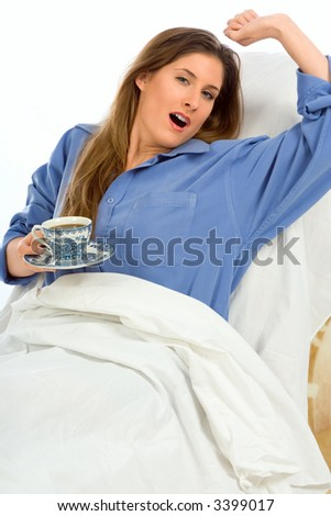 Young woman drinking coffee in the bed (focus on cup) - stock photo