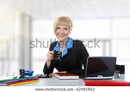 Young woman drinking coffee in the office. - stock photo
