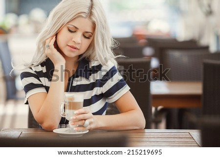 Young woman drinking coffee latte in a trendy cafe. woman drinking coffee in the morning at restaurant.