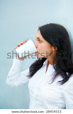 Young woman drinking coffee leaning to wall
