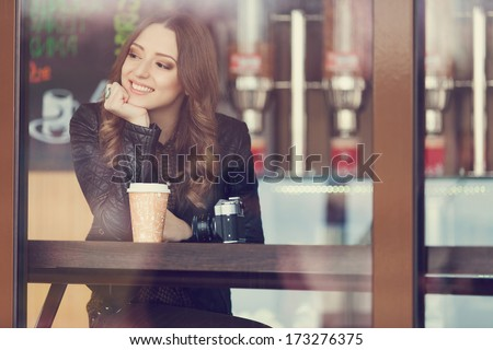 Young woman drinking coffee sitting indoor in urban cafe. Cafe city lifestyle. Casual portrait of teenager girl. Toned. - stock photo