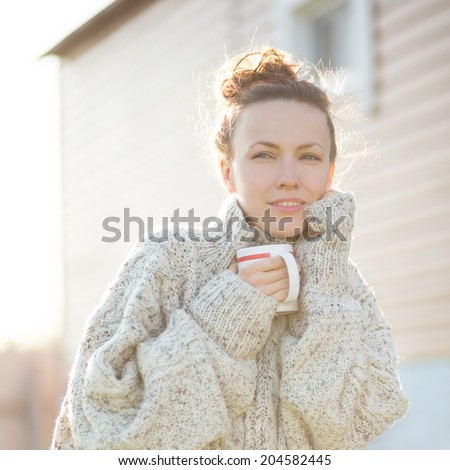 Young woman drinking coffee tea early in the morning in sunshine enjoying her morning tea. soft backlight - stock photo