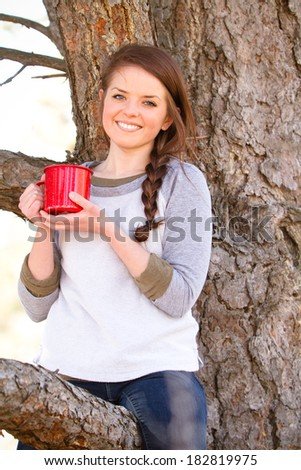 Young Woman Drinking Coffee - This is a photo of a cute you woman sitting in a tree enjoying a cup of coffee. Shot with natural light and a shallow depth of field. - stock photo
