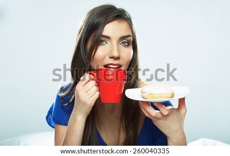 Young woman drinking coffee with donut. Beautiful female model with long hair. - stock photo