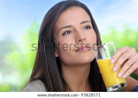 Young woman drinking fresh fruit juice - stock photo