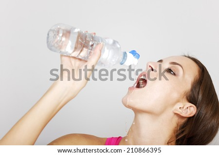 Young woman drinking from a water bottle after a long workout