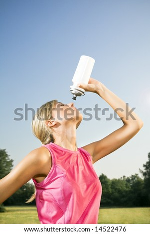 Young woman drinking from water bottle outdoors after jogging, copy space - stock photo