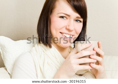 Young woman drinking hot tea - stock photo