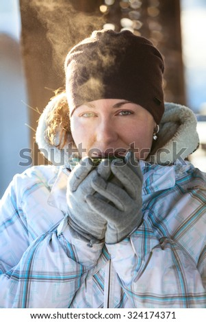 Young woman drinking hot tea from mug holding it in hands with mittens, winter season, outdoors - stock photo