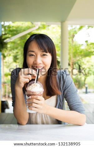 Young woman drinking ice coffee at restaurant - stock photo