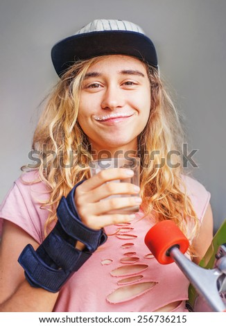 young woman drinking milk and holding a skateboard - stock photo