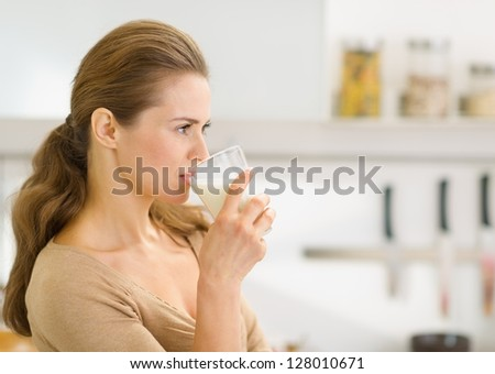 Young woman drinking milk in modern kitchen - stock photo