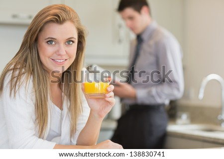 Young woman drinking orange juice in kitchen with husband reading newspaper - stock photo