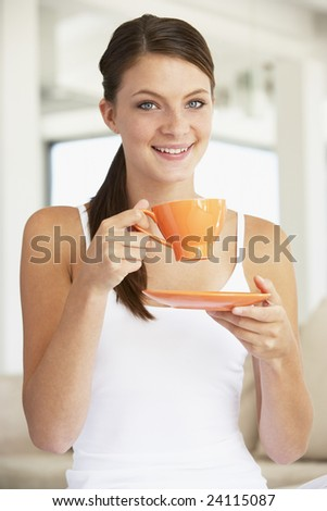 Young Woman Drinking Out Of An Orange Cup - stock photo