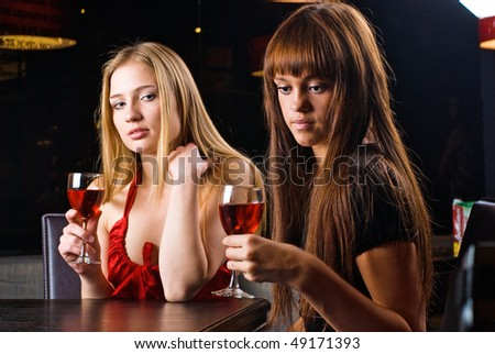 Young woman drinking red wine in bar