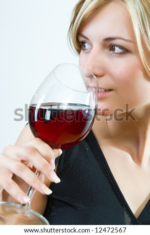 Young woman drinking red wine - white background