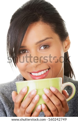 Young woman drinking something from big mug, isolated on white - stock photo