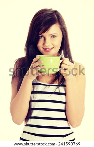 Young woman drinking something hot from big mug - stock photo