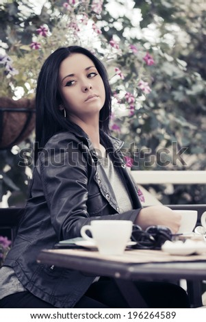 Young woman drinking tea at sidewalk cafe  - stock photo