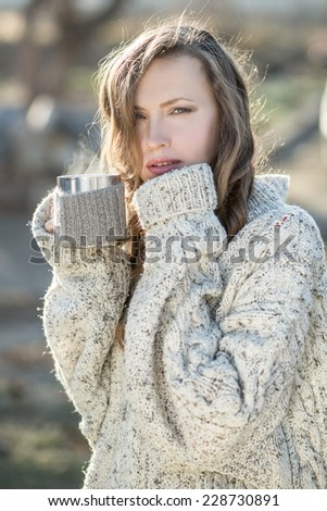 Young woman drinking tea early in the morning in sunshine enjoying her morning tea. backlit. sunshine - stock photo