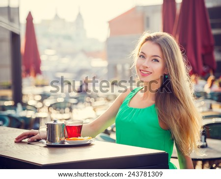 Young Woman Drinking Tea in a Cafe Outdoors. Summer City Background. Shallow Depth of Field. Toned Photo. - stock photo