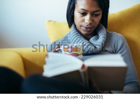 Young woman drinking tea reading book on couch - stock photo