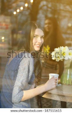 Young woman drinking tea sitting indoor in urban cafe. Cafe city lifestyle. Casual portrait of beautiful girl with spring flowers. Toned. - stock photo