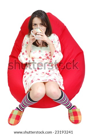 Young woman drinking tea while relaxing in a lazy bag - stock photo