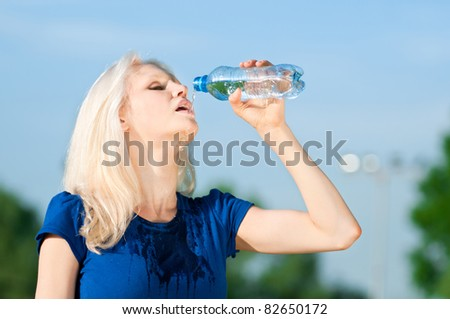 Young woman drinking water after fitness exercise