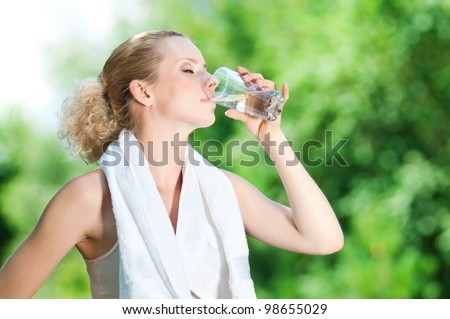 Young woman drinking water after fitness exercise - stock photo