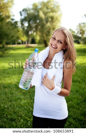 Young woman drinking water after training - stock photo