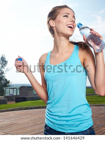 Young woman drinking water at outdoors workout