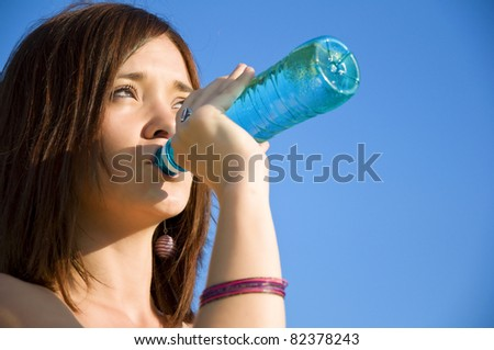 Young woman drinking water at outdoors workout - stock photo