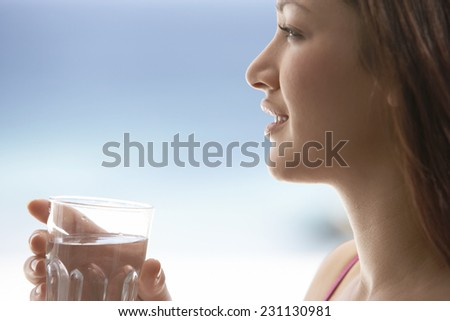 Young Woman Drinking Water by Sea - stock photo