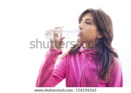 Young woman drinking water from a bottle wearing a pink fleece jacket after doing some exercise
