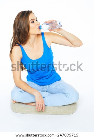Young woman drinking water from bottle, sitting on a floor in yoga pose. Portrait of female model with long hair isolated on white background. - stock photo