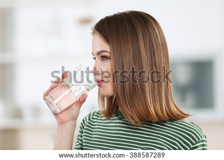 Young woman drinking water from glass in the kitchen - stock photo
