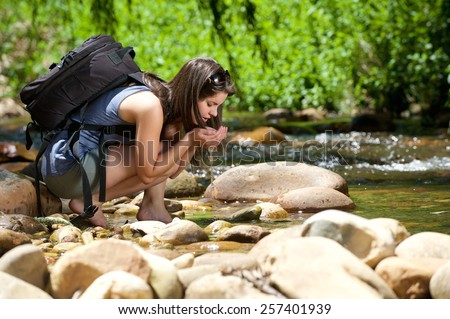 Young woman drinking water from outdoor stream with her hands - stock photo