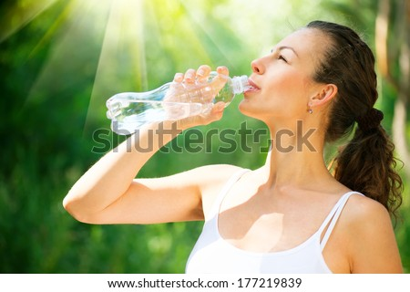 Young Woman Drinking Water from the bottle. Healthy and Sporty Girl Doing Sport Outdoor. Workout - stock photo