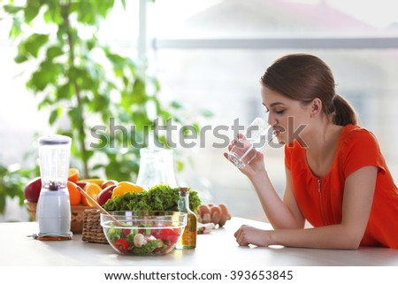 Young woman drinking water near table with fruits and vegetables in the kitchen - stock photo