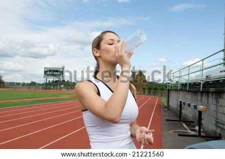 Young woman drinking water out of a water bottle at a track. Horizontally framed photo